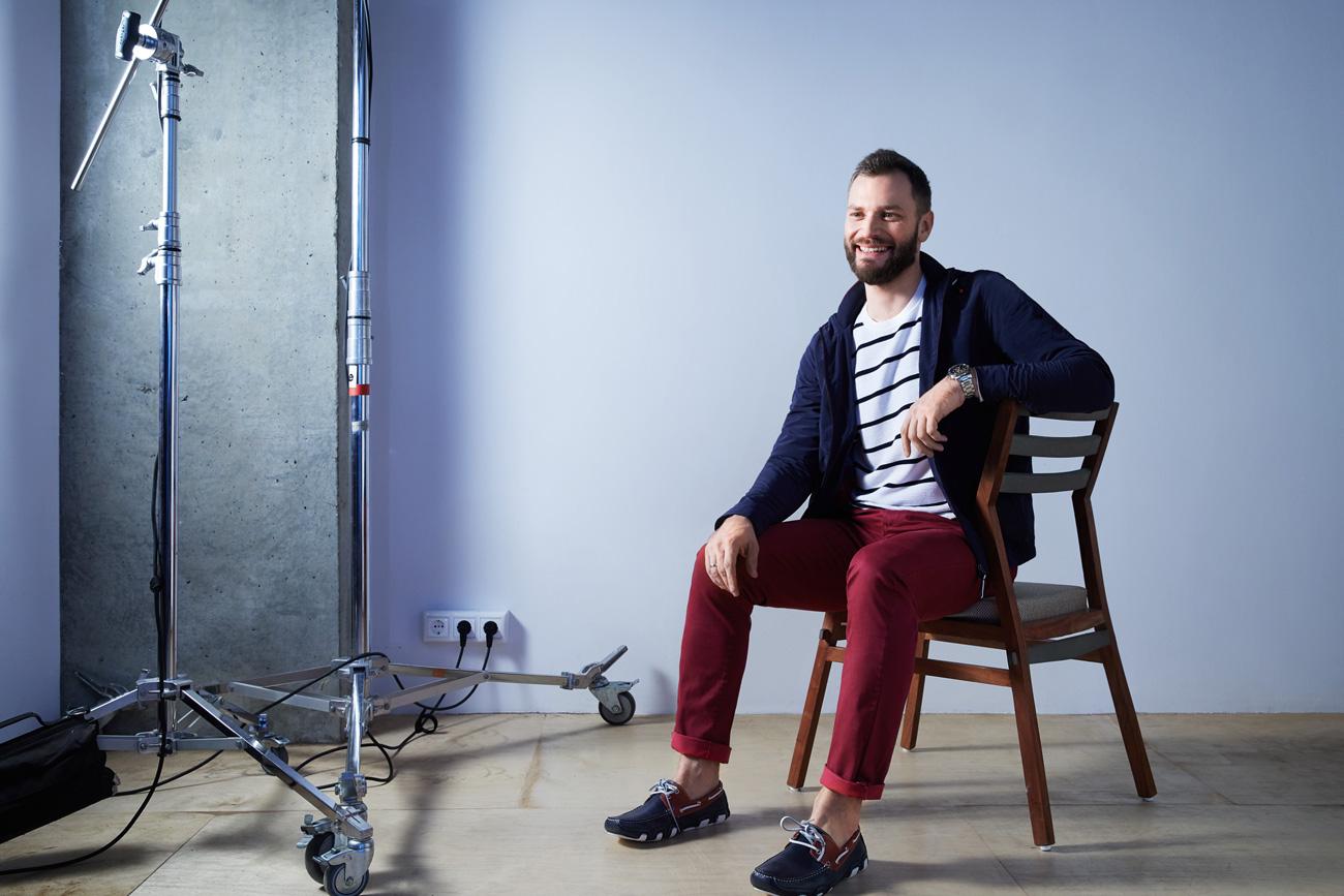На Юрии: синяя куртка, белый трикотаж, красные брюки, обувь — всё Henderson.