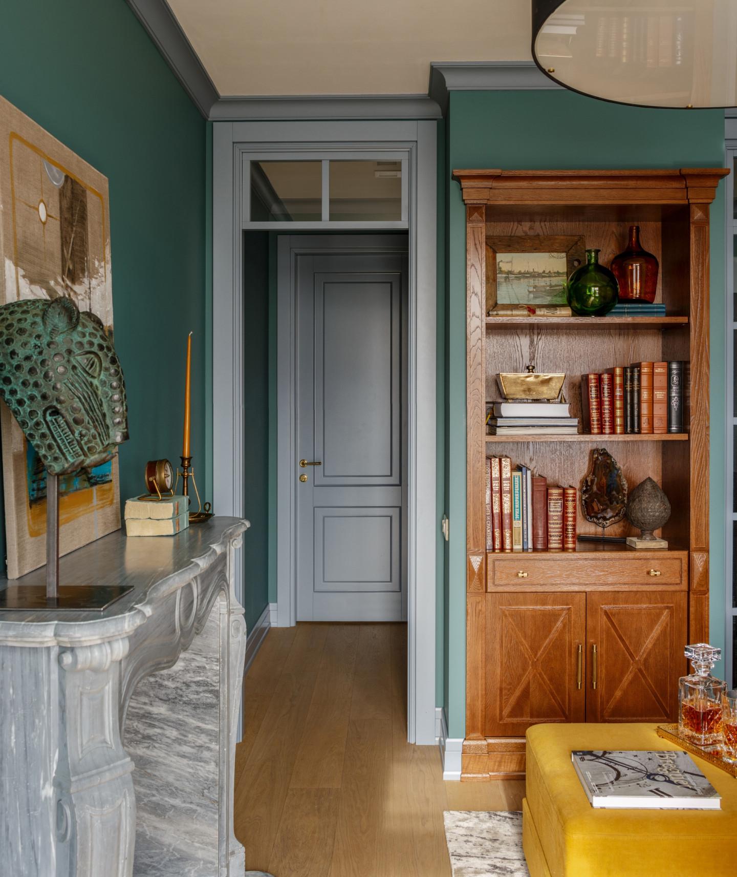 Традиционно декоративный камин располагают в гостиной (где он часто заменяет телевизор), но в этом интерьере дизайнер нашла для него место в кабинете