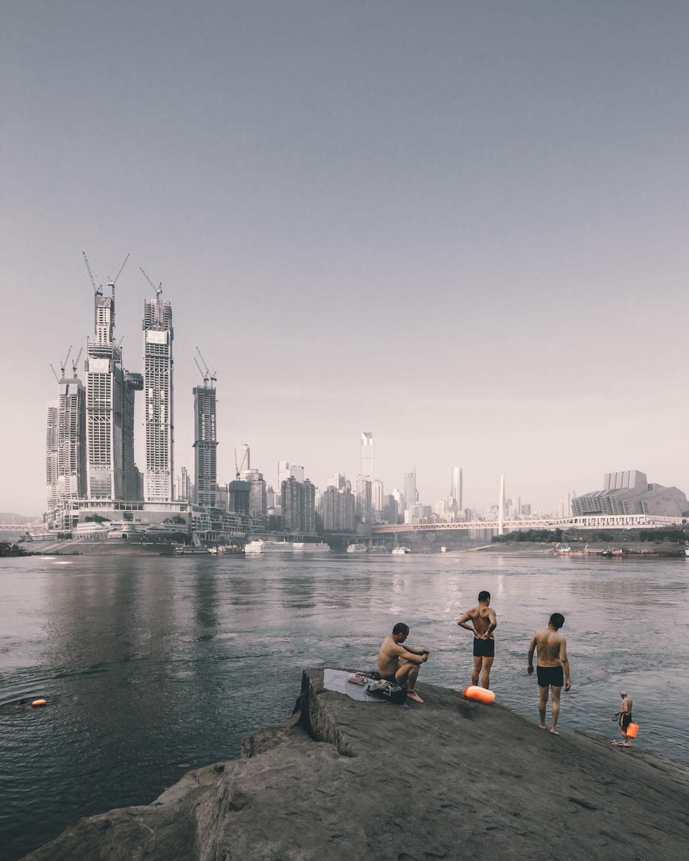 Ныряльщики на берегу реки напротив делового комплексаRaffles City Chongqing в Сингапуре. Категория«Ощущение места»