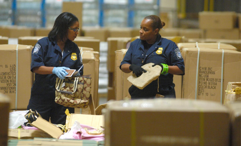 Сотрудники инспекции таможенного и пограничного контроля просматривают коробки с подозрительными товарами