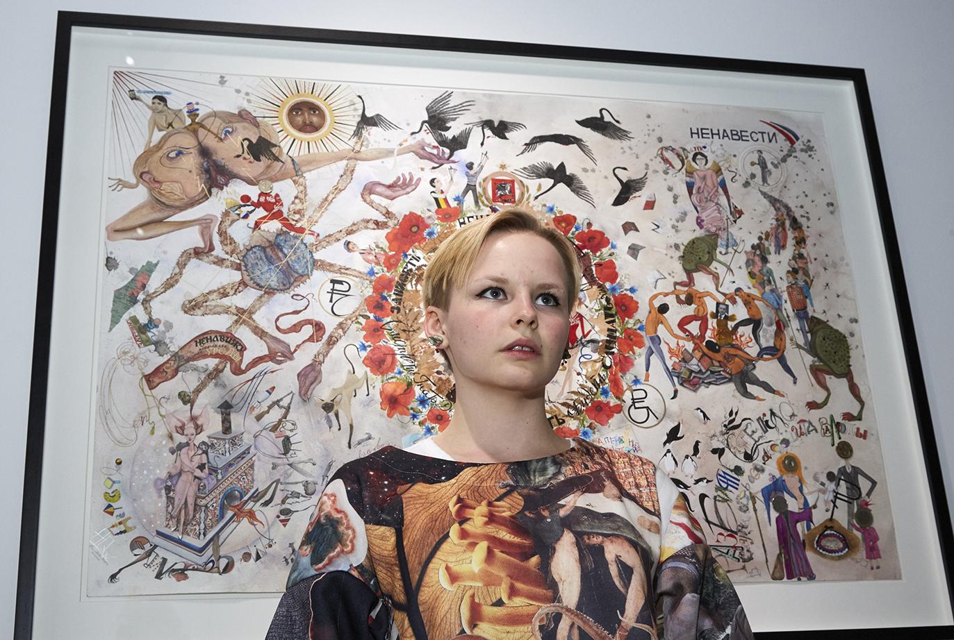Художница Таня Пеникер на фоне своей графической работы «Третья мировая войнушка»