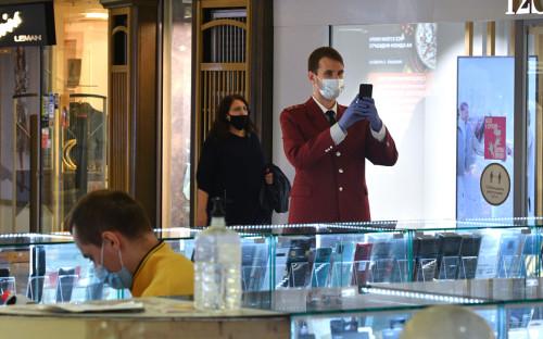 Сотрудник Роспотребнадзора (справа) проверяет соблюдение масочного режима в торговом центре «Охотный ряд» в Москве