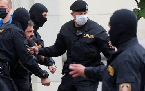 Сотрудники правоохранительных органов задерживают человека у здания белорусской избирательной комиссии