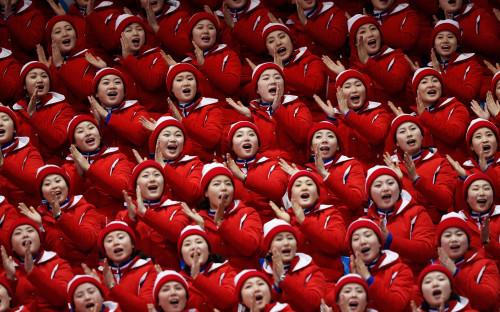 """<p>Едва&nbsp;ли не больше самой Олимпиады запомнятся болельщицы Северной Кореи. Впервые с 2006 года КНДР и Южная Корея объединились для участия в Играх. КНДР привезла в Южную Корею группу поддержки из 229 девушек. Все они одеты в форму, на трибунах синхронно кричат лозунги и демонстрируют танцевальные движения. Как <a href=""""https://www.nytimes.com/2018/02/12/sports/olympics/north-korean-cheerleaders.html"""">пишет</a> The New York Times, болельщицы разделены на группы, каждую из которых сопровождают несколько мужчин. Без сопровождения болельщицы не появляются нигде и не общаются ни с кем, кроме друг друга. У них есть заводила, по команде которого они начинают кричать и хлопать.</p>  <p>Как рассказала изданию женщина, которой несколько лет назад удалось бежать из КНДР, она тоже когда-то была такой чирлидершей. По ее словам, девушек отбирают из спортивных и танцевальных секций, они обязательно должны быть выше 160&nbsp;см, а также быть благонадежными и доказать верность режиму. За выступления на соревнованиях им не платят, а на подготовку к ним уходит несколько месяцев.</p>"""