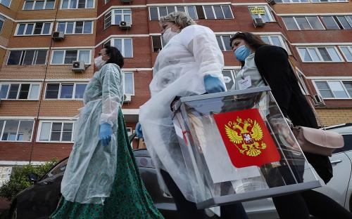 Сотрудники участковой избирательной комиссии с переносным ящиком для голосования