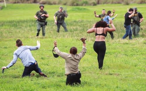 Офицеры полиции встречают людей, выбежавших на поле возле аэропорта после стрельбы