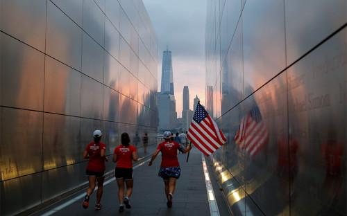 <p>Люди с&nbsp;флагом США бегут сквозь&nbsp;государственный мемориал &laquo;Пустое небо&raquo; в&nbsp;Нью-Йорке, посвященный памяти жертв терактов 11 сентября. Нью-Йорк, США</p>