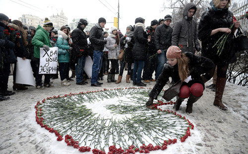Участники акции солидарности с журналистами Charlie Hebdo создают сердце из цветов у посольства Франции в Москве