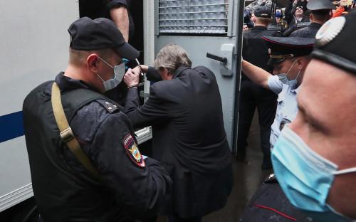 Михаил Ефремов в сопровождении конвоя заходит в полицейский автозак у здания Пресненского суда