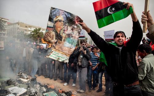 """<p>15 февраля 2011 года в Бенгази, втором по величине городе Ливии, начались народные волнения, вызванные задержанием юриста и правозащитника Фатхи Тербиля. Антиправительственные протесты перешли в вооруженные столкновения с полицией по всей стране. 27 февраля повстанцами был сформирован переходный национальный совет республики, признанный тогда большинством стран мира единственным легитимным органом власти.</p>  <p>18 марта 2011 года Совет Безопасности ООН <a href=""""http://www.interfax.ru/russia/182092"""">принял</a> резолюцию 1973, санкционировавшую&nbsp;военное вмешательство иностранных государств в ливийский конфликт и&nbsp;одобрившую создание бесполетной зоны. Военную операцию сначала вела коалиция во главе с США, а в конце марта контроль над ней&nbsp;перешел к НАТО.</p>  <p>В конце августа повстанцам удалось взять столицу. 20 октября во время штурма города Сирт был убит Муаммар Каддафи, правивший страной c 1969 года.</p>  <p></p>"""