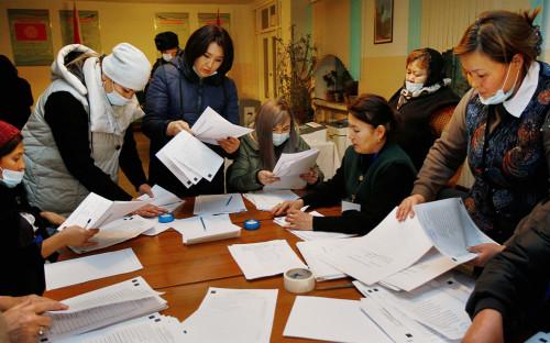 Сотрудники избирательной комиссии во время подсчёта голосов на одном из избирательных участков в Бишкеке после окончания голосования на досрочных выборах президента Кыргызской Республики и референдуме по вопросу формы правления