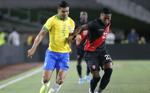 Полузащитник сборной Перу Педро Акино (справа) против хавбека бразильского национальной команды Каземиро