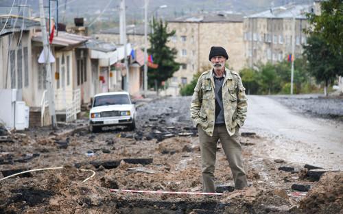 Мужчина на улице, пострадавшей в результате недавнего обстрела в Степанакерте