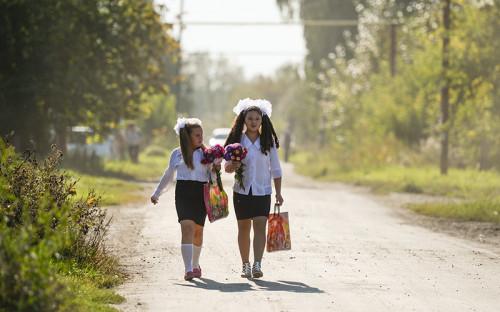 Дети идут в школу на торжественную линейку, посвященную Дню знаний, в село Новолуговое Новосибирской области