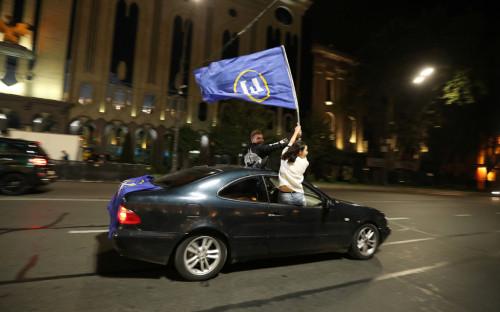 Сторонники правящей партии «Грузинская мечта» празднуют победу, после объявления экзитполов парламентских выборов в Тбилиси
