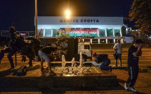 Участники протестов промывают глаза от слезоточивого газа после столкновений с ОМОНом