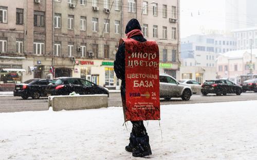 """<p><span style=""""font-size:18px;""""><strong>Зазывала</strong></span></p>  <p>Важный участник цветочного рынка&nbsp;&mdash;&nbsp;зазывала. В Москве они есть практически у всех крупных цветочных сетей. Цель зазывал&nbsp;&mdash;&nbsp;показать покупателям, что&nbsp;неподалеку есть цветочный магазин, и&nbsp;указать, где&nbsp;именно, так как&nbsp;сами магазины-склады, как&nbsp;правило, располагаются во&nbsp;дворах или&nbsp;подвалах.</p>  <p>Герой кадра приехал на&nbsp;учебу из&nbsp;Африки&nbsp;и&nbsp;теперь прячет лицо за&nbsp;толстым шарфом от&nbsp;холода. Его доход&nbsp;&mdash;&nbsp;рубль за&nbsp;каждую листовку. За час он должен раздать 150 штук. Всего&nbsp;же&nbsp;его рабочий день длится семь часов.</p>"""