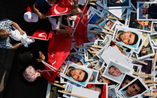 <p>Люди перед началом Марша национального единства в Стамбуле выбирают баннеры с изображениями жертв неудачной попытки госпереворота в 2016 году. Тогда в Турции погибли 250 человек, которые пытались противостоять заговорщикам.</p>