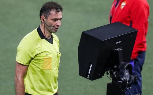 Судья Алексей Еськов смотрит видеоповтор игрового момента на мониторе системы видеопомощи арбитрам (VAR) на матче чемпионата России по футболу
