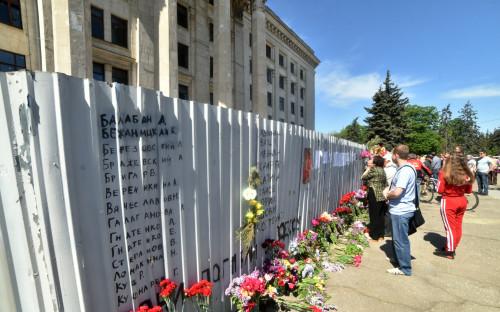 Люди возлагают цветы у Дома профсоюзов в память о погибших