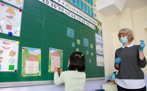 Школьница выполняет классные задания под руководством своего учителя в научно-образовательном школьном комплексе Ломоносов в Бишкеке