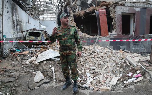 Азербайджанский военнослужащий около здания, разрушенного в результате обстрела города Гянджа