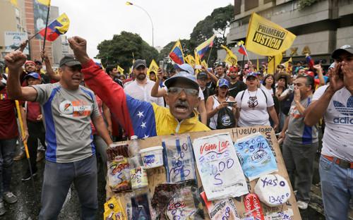 <p>Участник оппозиционнного митинга держит плакат с ценами на продукты. В Венесуэле дефицит продуктов питания и медикаментов. Минимальная зарплата в стране составляет $30 в месяц</p>