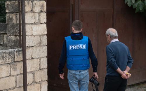 Представитель СМИ и местный житель осматривают пострадавший дом в городе Мартуни после обстрелов