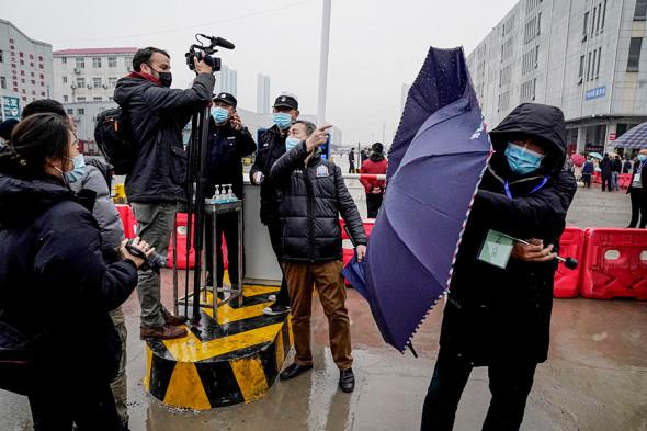 Журналисты снимают работу экспертов ВОЗ на крупнейшем в городе рынке Байшачжоу, где продают свежее мясо, рыбу и морепродукты, 31 января