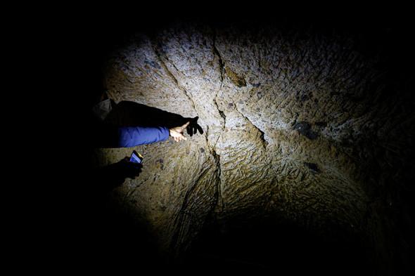 Геолог показывает на трещины в скале