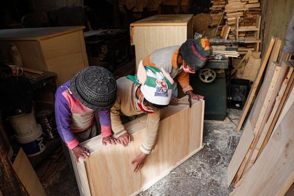 Дети работают в столярной мастерской своей семьи в Эль-Альто, Боливия, сентябрь 2020 года