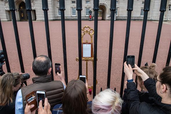 Люди фотографируют официальное объявление о рождении сына герцога и герцогини Сассекских, 7 мая
