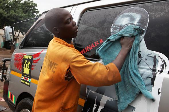 Молодой человек смывает изображение президента Мугабе со своей машины