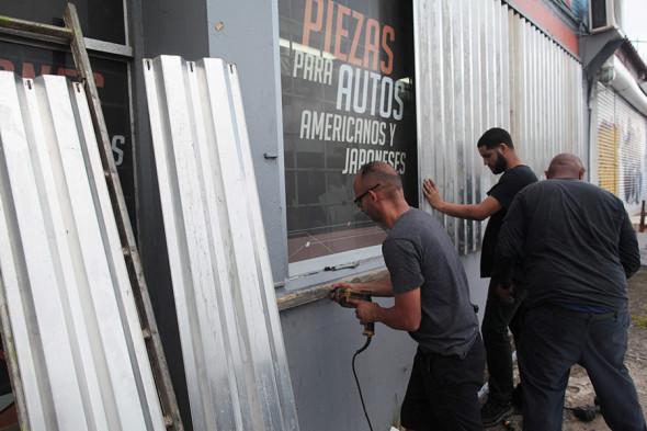 Рабочие закрывают окна профнастилом в Сан-Хуане