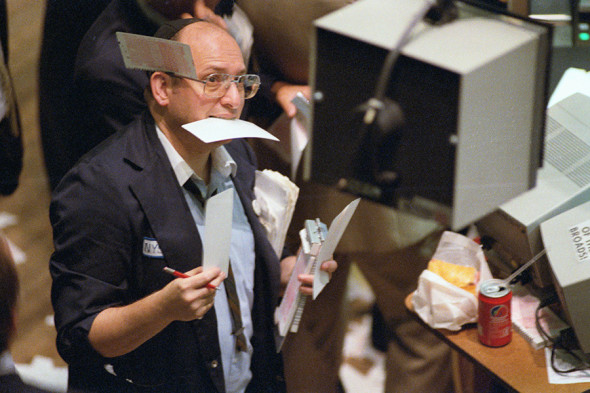 (Original Caption) New York: As busy as a beaver once again 9/12 a floorman at the New York Stock Exchange takes orders during record volume day that saw the Dow Jones industrial average rise and fall like a roller coaster.