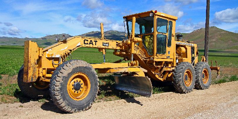 Землеройно-планировочная машина Caterpillar, которая с помощью отвала вырезает, перемещает и разравнивает грунт, снег и сыпучие строительные материалы