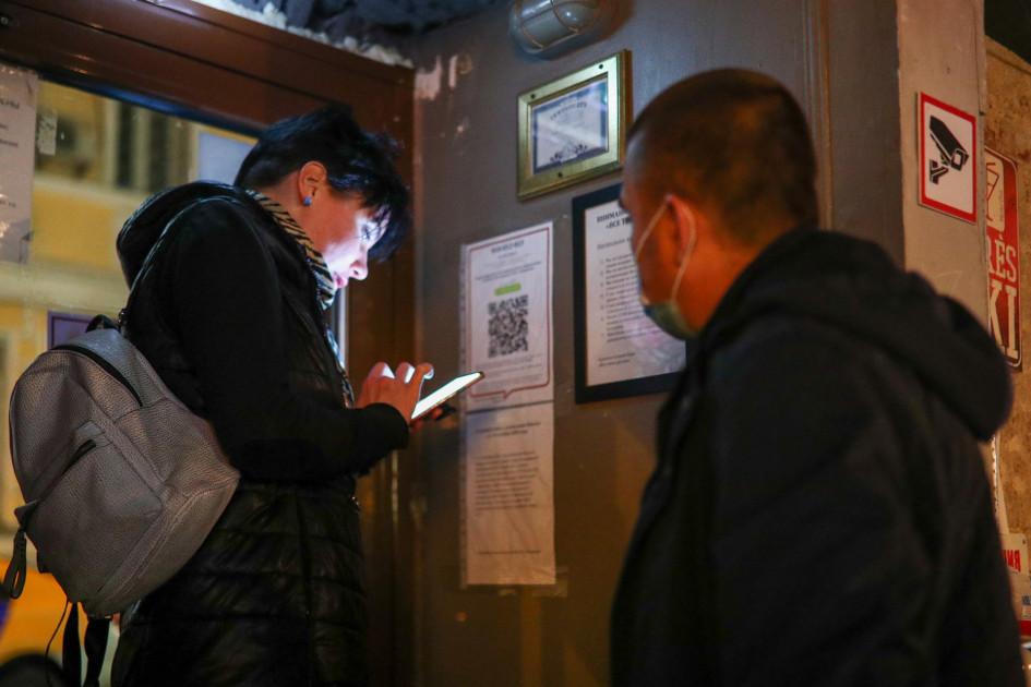 Женщина и сотрудник охраны возле входа в ночной клуб. Проходить регистрацию при входе в заведение посетителям и сотрудникам необходимо с 19 октября в любое время суток, в том числе в дневные часы