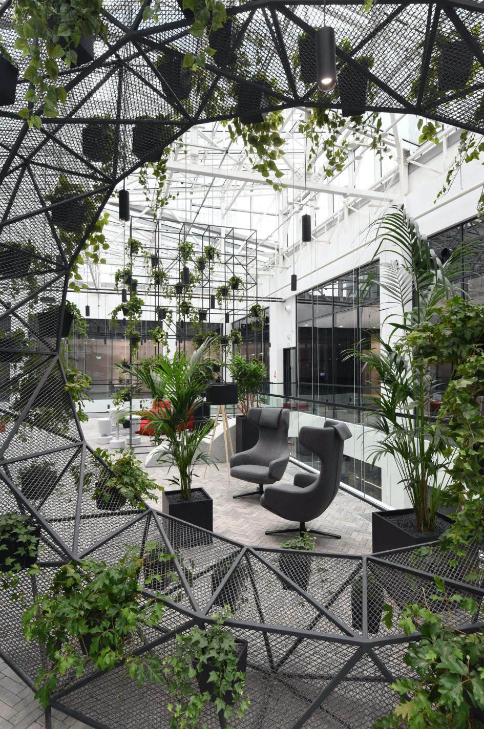Релакс-зона с зелеными растениями и мягкой мебелью.