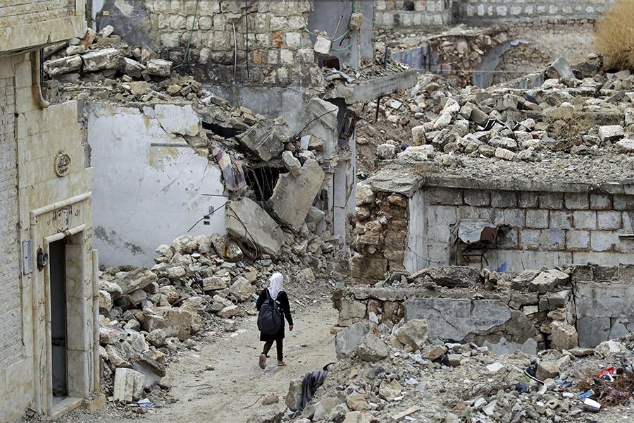 Сирийская школьница идет по разрушенному району Идлиба