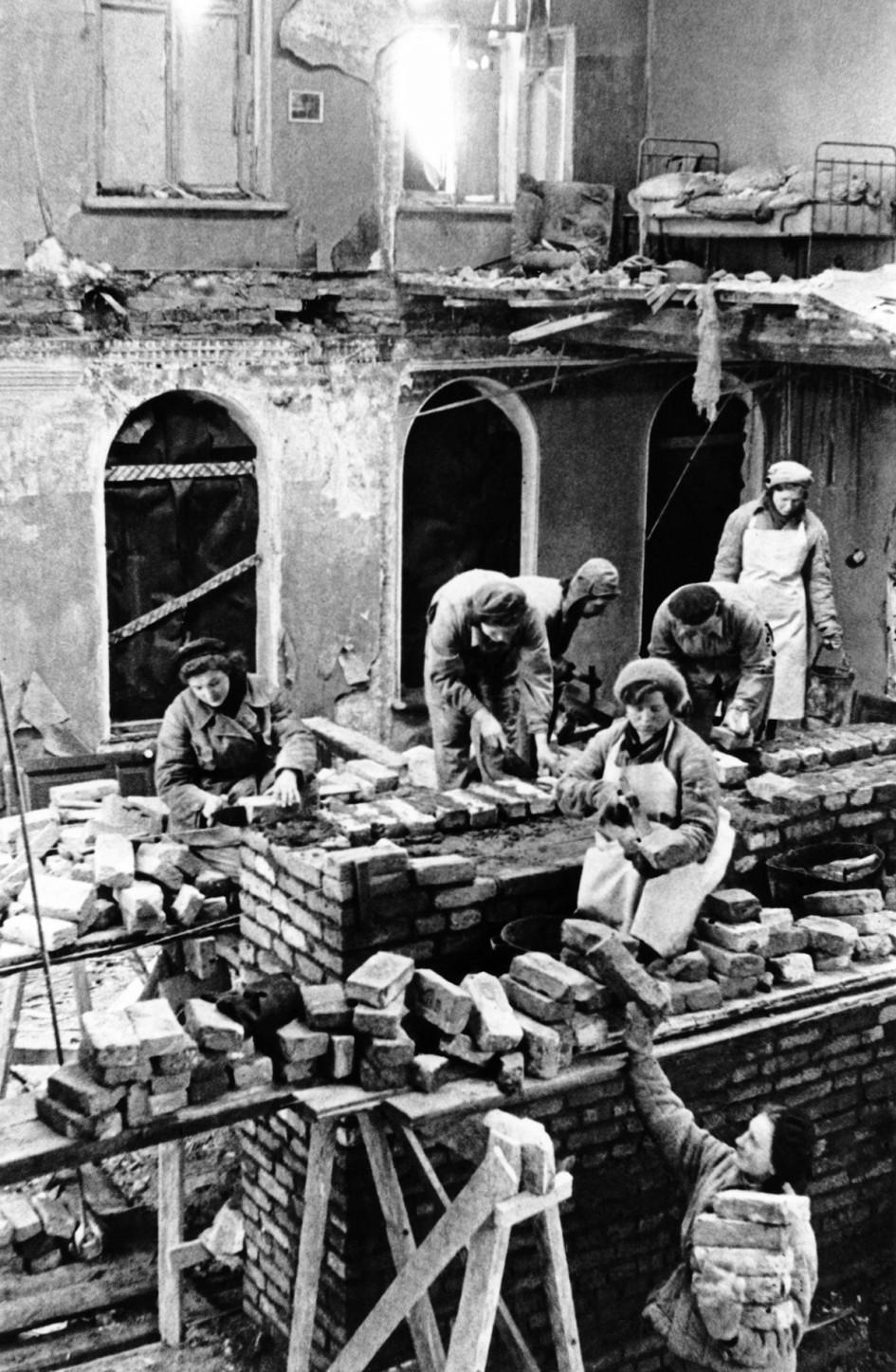 Бригада строителей Дзержинского района Ленинграда ремонтирует дом № 16 в Саперном переулке, пострадавший от артиллерийского обстрела. 1944 год