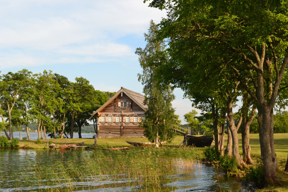Деревенский деревянный дом с лодкой на берегу Онежского озера, Карелия