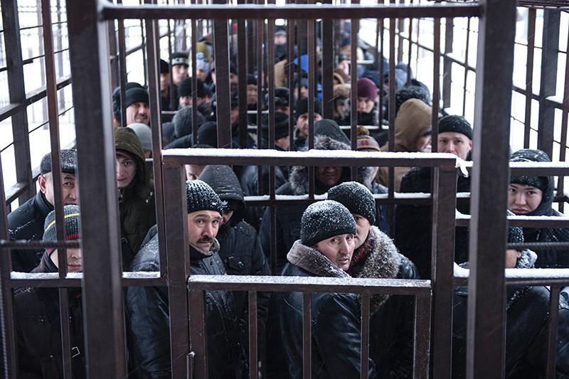 Мигранты из стран ближнего зарубежья стоят в очереди в одном из отделений Управления Федеральной миграционной службы (УФМС) по городу Москве