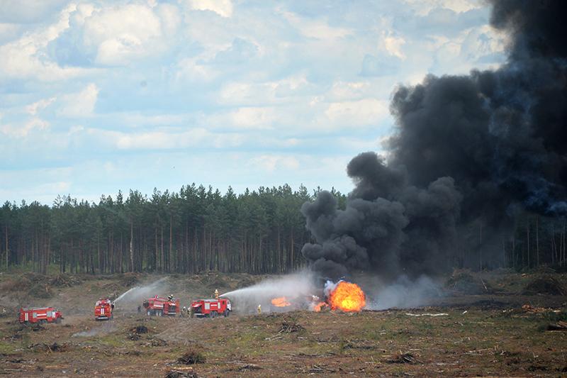 Сотрудники МЧС тушат пожар на месте крушения Ми-28 на полигоне «Дубровичи» в Рязанской области
