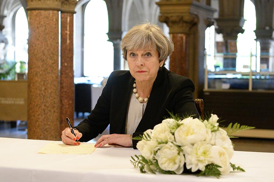 Премьер- министр Великобритании Тереза Мэй делает запись в книге соболезнований жертвам теракта