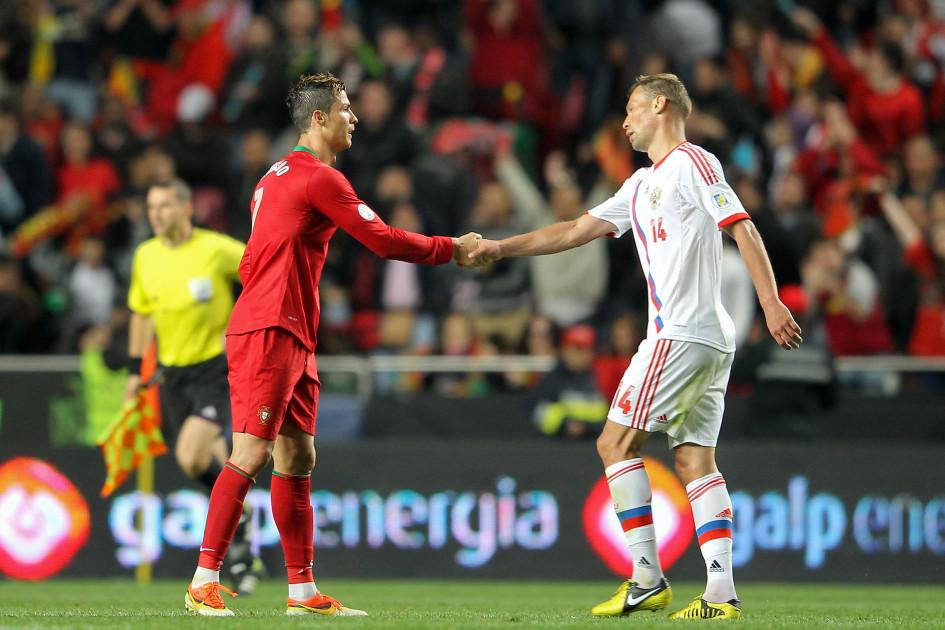 Криштиану Роналду (слева) и Василий Березуцкий в отборочном матче ЧМ-2014 в Лиссабоне