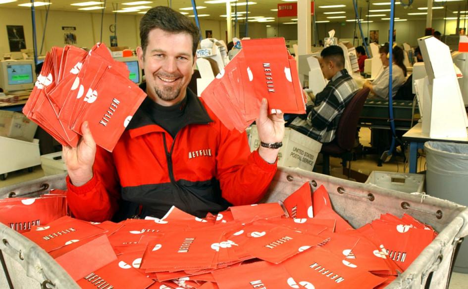 Генеральный директор Netflix Рид Хастингс сидит в тележке, полной готовых к отправке DVD-дисков 29 января 2002 года в Сан-Хосе, Калифорния, США