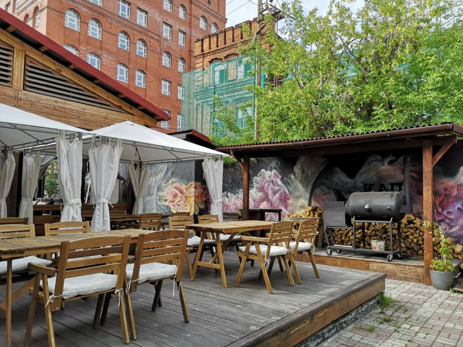 """Внутренний двор бара-коптильни """"Капчо"""" с видом на соседний памятник архитектуры."""