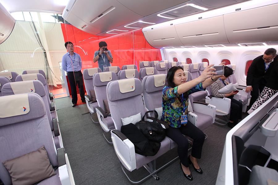 Посетители в полноразмерном макете российско-китайского широкофюзеляжного дальнемагистрального самолета CRAIC CR 929