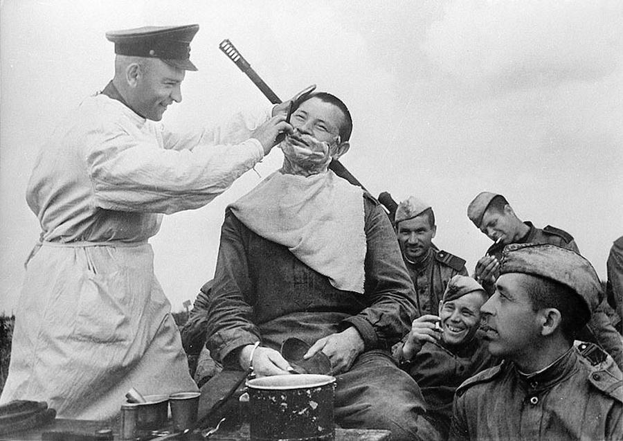 Зенитно-артиллерийская батарея лейтенанта Галанова: парикмахер Вильдерман бреет красноармейца Хамидулина в перерыве между боями, 1943 год. Автор: Наум Грановский