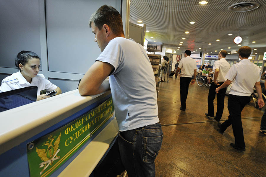 Пассажир у мобильного пункта Федеральной службы судебных приставов в терминале F аэропорта «Шереметьево»